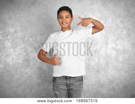 Young African American boy in blank white t-shirt standing against textured wall