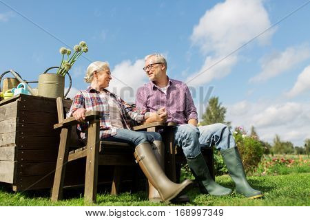 farming, gardening, old age and people concept - happy senior couple at summer farm