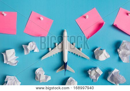 Airplane model flying among paper clouds and pink paper noted Traveling concept