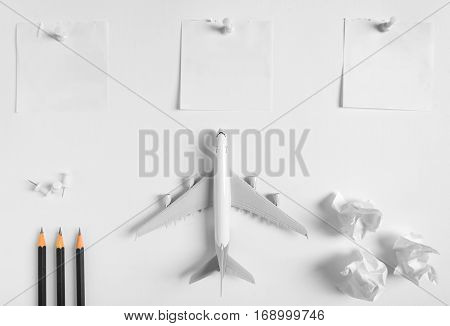 Preparation for Traveling concept and to do list blank paper noted paper ball airplane push pin pencils on white background with copy space.