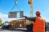 Construction industrial worker operating hoisting process of concrete slab poster