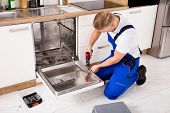 Young Repairman Service Worker Repairing Dishwasher Appliance In Kitchen poster