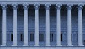 A building facade with corinthian columns in a row (colonnade). The neoclassical building style resembles a law court / courthouse, university, library or public administration building. Blue color tone. poster