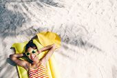 Child girl in yellow swimwear and sunglasses chilling on lilo under palm tree on sand at the beach. Tropical island. Summer holiday idyllic. Top view. poster