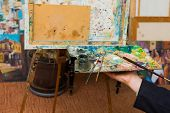 Artist hand holding palette with mixed pigment and paintbrushes ready to paint on canvas. poster