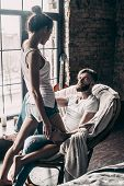 Love and passion. Attractive young woman flirting with her boyfriend while standing in front of him at home poster