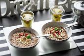 Chocolatiers breakfast for two person with oatmeal, puffed rice, cereals , dried strawberries and  tea prepared in a white bowl. Big inscription Dream above. poster