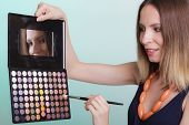 Woman stylist applying eyeshadow with professional makeup palette and brush. Girl beautyfying eye eyelid. Make up makeover concept. poster