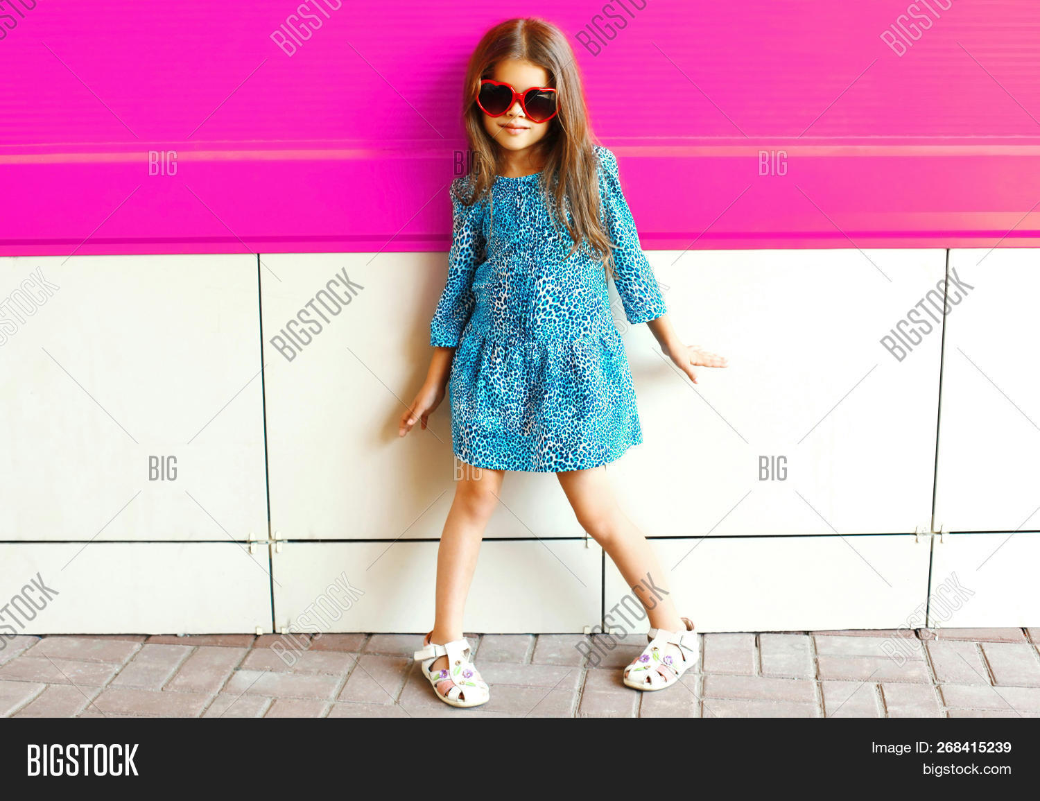 4c55839c6c40 Beautiful little girl child posing on city street on colorful pink wall  background