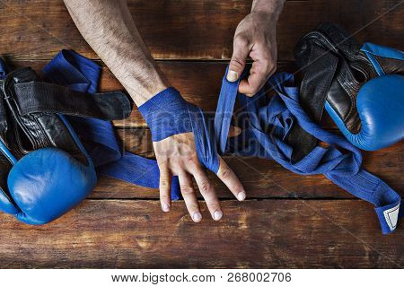 Man Bandage Boxing Tape On His Hands Before The Boxing Match On A Wooden Background. The Concept Of