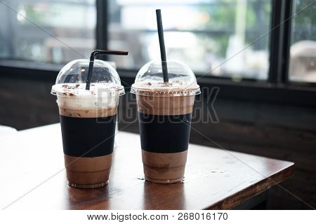 Two Plastic Take Away Cup Of Iced Coffee Mocha And Iced Chocolate On Wood Table In Coffee Shop