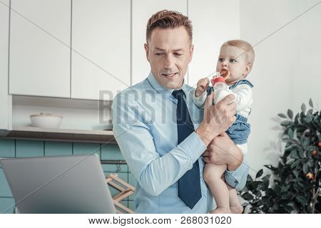 Occupied Focused Man Holding A Baby Being At Home.
