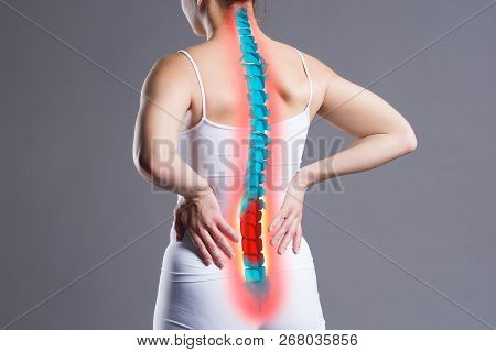 Pain In The Spine, Woman With Backache On Gray Background, Back Injury, Photo With Highlighted Skele