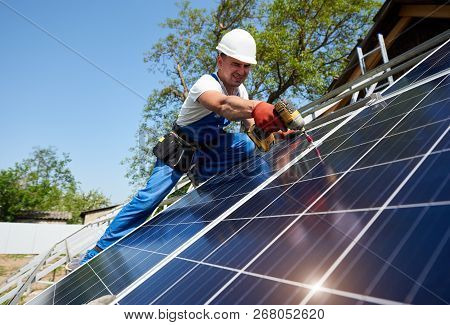 Technician Installing Solar Photo Voltaic Panel To Metal Platform Using Screwdriver On Bright Blue S