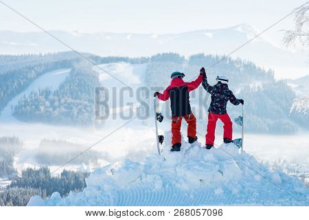 Shot Of A Couple High Fiving Each Other Posing On Top Of A Snowy Mountain Observing Stunning Winter