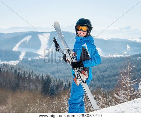 Happy Female Skier Smiling To The Camera, Holding Her Skis, Wearing Blue Ski Suit And Black Helmet A