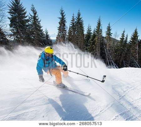 Action Shot Of Professional Skier Taking Selfies Photo With A Camera On Selfie Stick While Skiing On