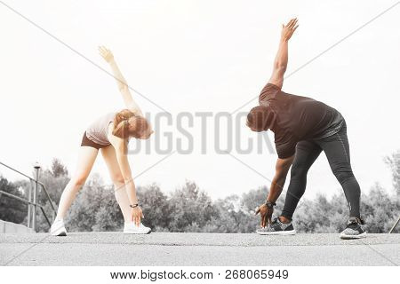 A Pair Of Athletes Do A Warm-up. A Loving Couple An African American Man And A European Woman Are Sp