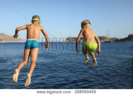 Two happy boys in goggles jump into blue sea water, back view