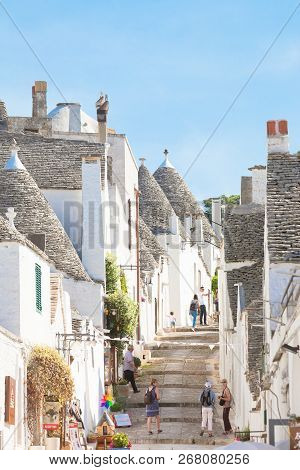 Alberobello, Apulia, Italy - June 1, 2017 - Tourists Walking Through A Traditional Alleyway In The O