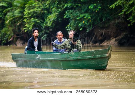 05 October 2013 Sabah. Borneo. Malaysia. A Photographer With A Long Lens Travels By Boat Along The K