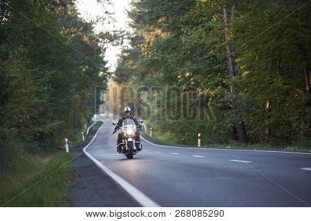 Bearded Biker In Sunglasses, Helmet And Black Leather Clothing Riding Modern Powerful High-speed Mot