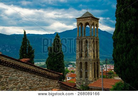 Bell Tower And Cypress Trees Near Church In Front Of Mountains And Cloudy Sky In Town Kalabaka, Gree