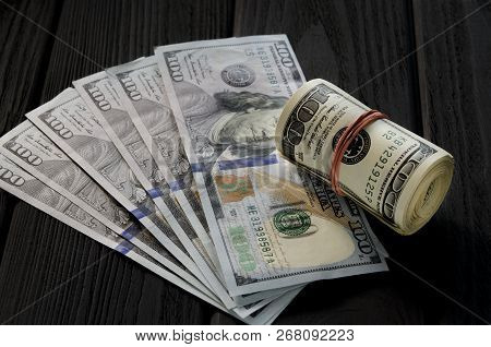 A Thick Roll Of Old Hundred Dollar Banknotes Tied A Red Rubber Band Lies On The Whisker Of New Hundr
