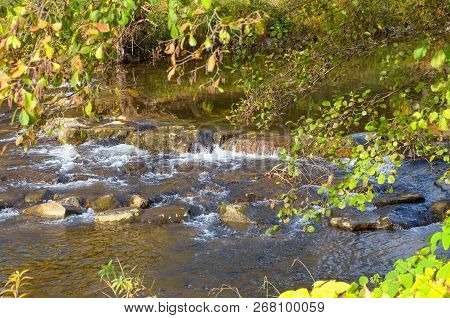 Picturesque Waterfall On A Fast Flowing Stream Cascading Over A Rocky Ledge In Autumn In Glowing Eve