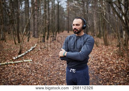 Athlete Jogging In The Woods. A Young Man With Headphones Running In The Woods. Autumn
