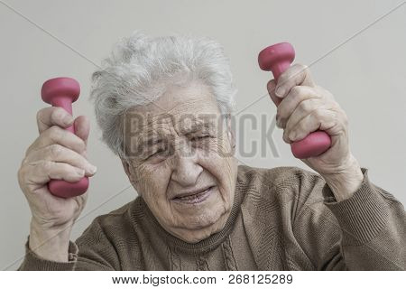 Senior Woman Has Difficulty To Lifting Dumbbells