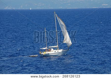 PAXOS, GREECE - JUNE 19, 2014: A yacht sails off the coast of Lakka on the Greek island of Paxos. The 13km long island is a popular sailing destination.