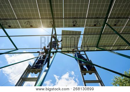 Installing Innovative Solar Batteries By Workers. Standing On High Ladder. Sunny Weather, Blue Sky.