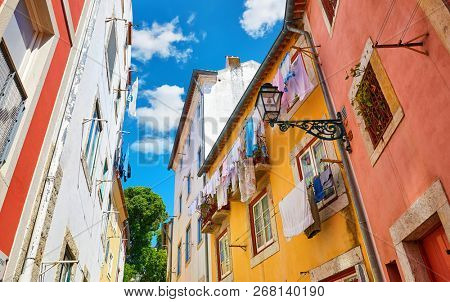 Lisbon, Portugal. Antique Alfama district with coloured houses on background of blue sky with clouds. Washed linen dry on ropes on streets between building. Decorative street lamp on the wall.