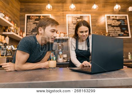Young Couple Man And Woman Owners Of Small Modern Coffee House Using Laptop Computer For Work.