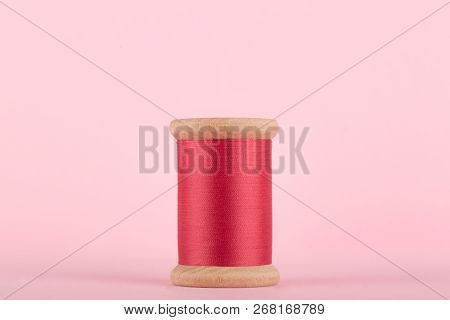 Pink Thread, Cerise Pink Wooden Thread Bobbin Isolated On Pastel Pink Background, Copy Space, Center