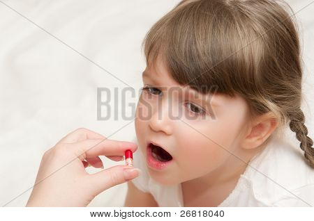 Woman give red pill to little girl