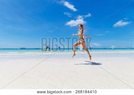 Beautiful Blonde Bride In A White Bikini And A Veil Having Fun On The Beach. Tropical Sea In The Bac