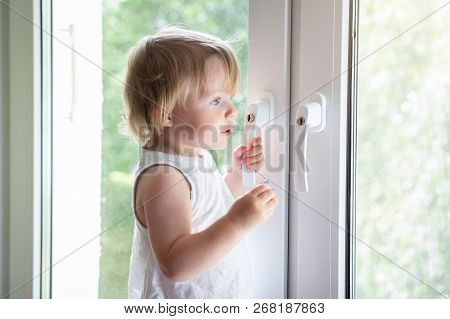 Little Baby Girl On Window Sill. Child Looks At Street Through Window