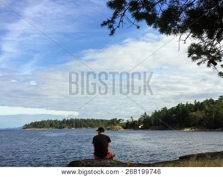 Man On An Island By The Shore Thinking And Contemplating Staring Out At The Ocean