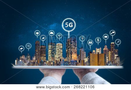 Hand Holding Digital Tablet With Modern Buildings Hologram And Technology Icons. Smart City, 5g, Int