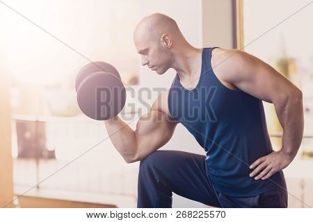 Pensive Man Doing Strength Exercise Dumbbell Hands. Physical Exercise On The Arms With The Help Of A