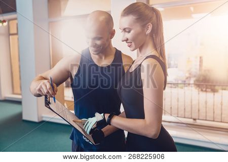 Trainer Writes A Fitness Program Training The Girl. The Program Of Physical Training For Effective R