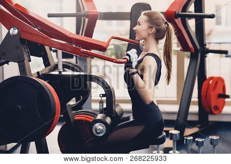 Girl Engaged The Training Apparatus For The Backs. A Happy Young Girl Performs A Physical Exercise O