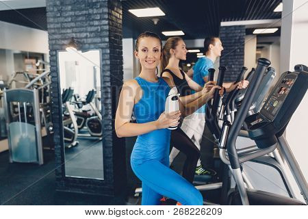 The girl is happy with her result on an elliptical trainer. Professional cardio training. Improving health through proper exercise in the gym. A group of people are training on an elliptical trainer poster