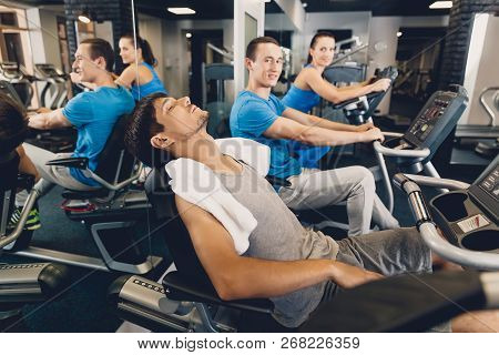 A Man Is Tired After Physical Training On Cardio. Men And Women Perform Physical Exercises On Cardio