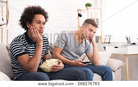 Bored Teens Watching Dull Movie With Popcorn At Home, Copy Space