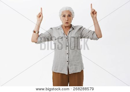 Indoro Shot Of Worried Questioned Granny With Grey Hair In Casual Shirt Raising Hands Pointing Up Fo