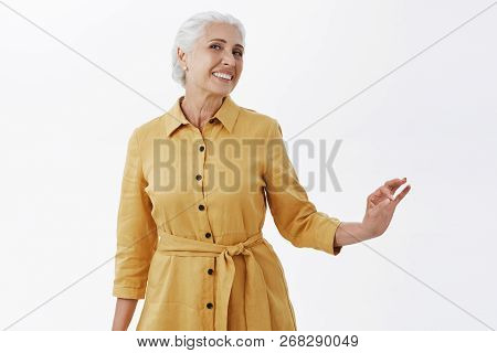 Indoor Shot Of Happy Stylish And Pretty Elegant Senior Woman In Trendy Yellow Coat Posing With Elleg