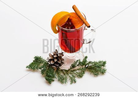 Mulled Wine In Glass Near Fir Cone And Branch. Beverage With Orange And Cinnamon. Glass With Mulled